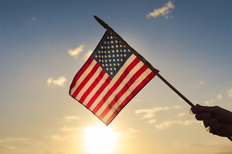 Hand Holding United States Flag Against Sunset