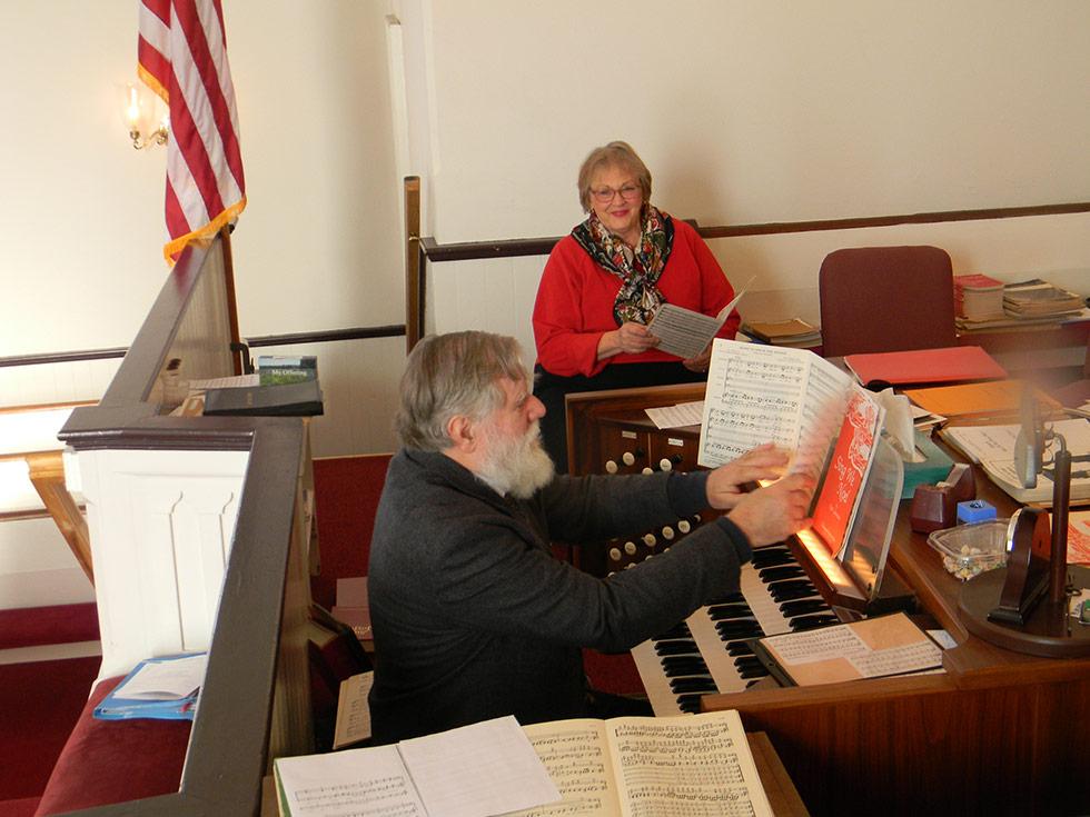 Music Director Charlie Confer Rehearses With Choir Member Cheri Christakis