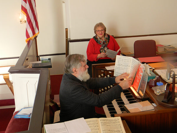 Music Director Charlie Confer Rehearses With Choir Member Cheri Christakis